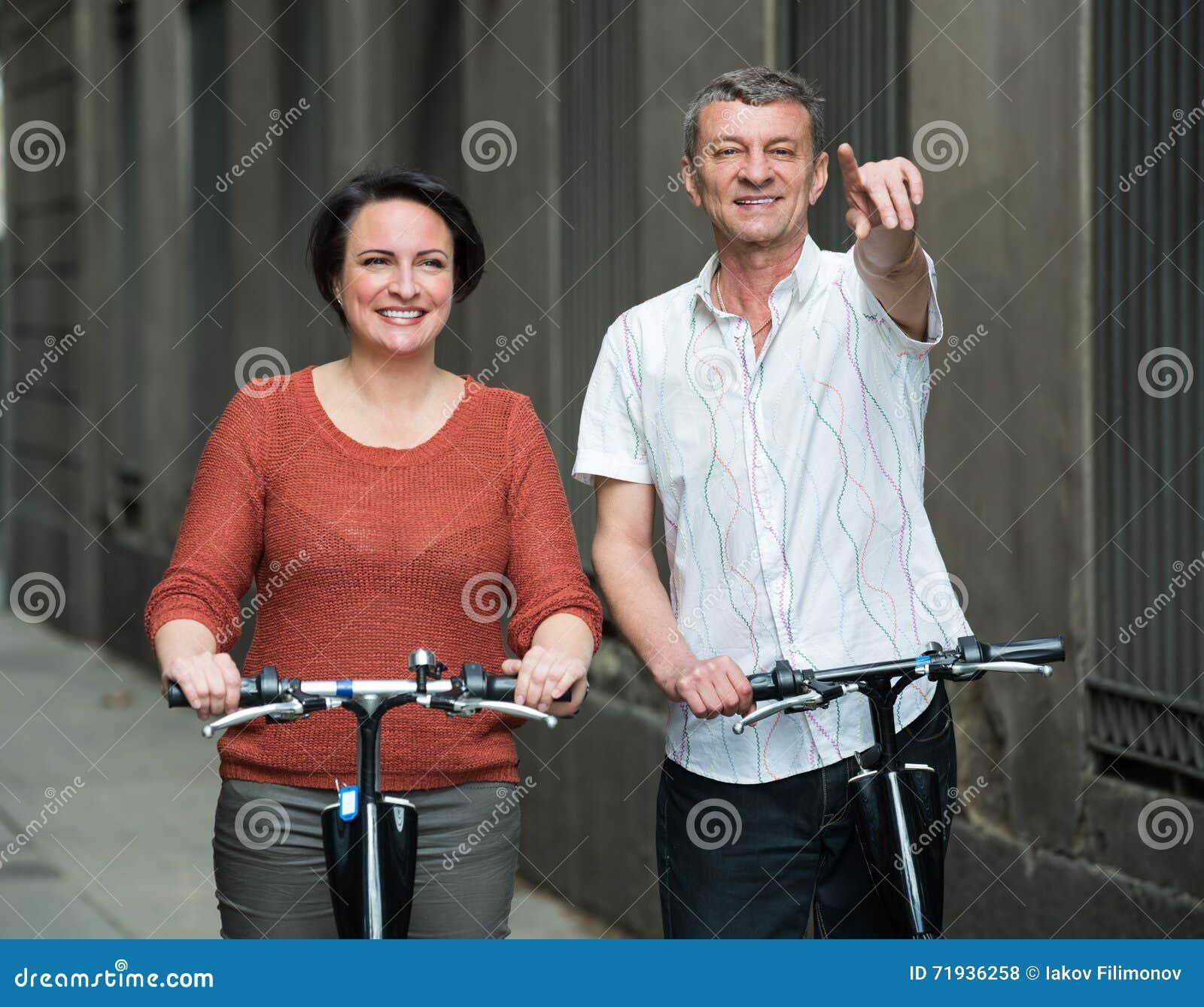 Зрелые пары оставаясь с электрическими велосипедами