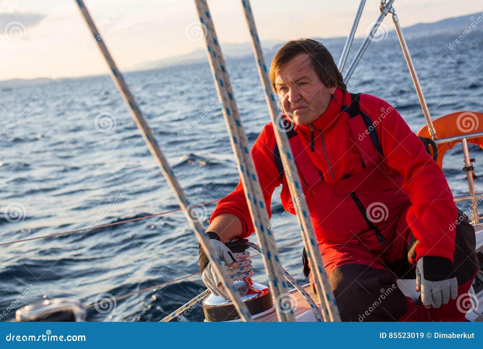 Зрелый мужской шкипер сидя на его яхте плавания Спорт