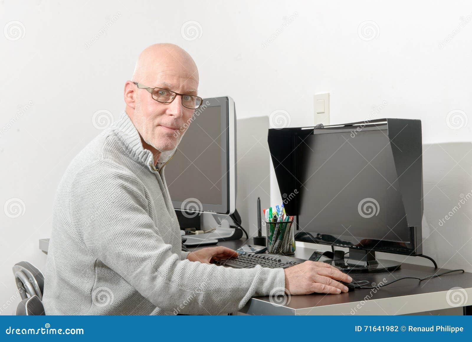 Зрелый человек работая с его компьютером