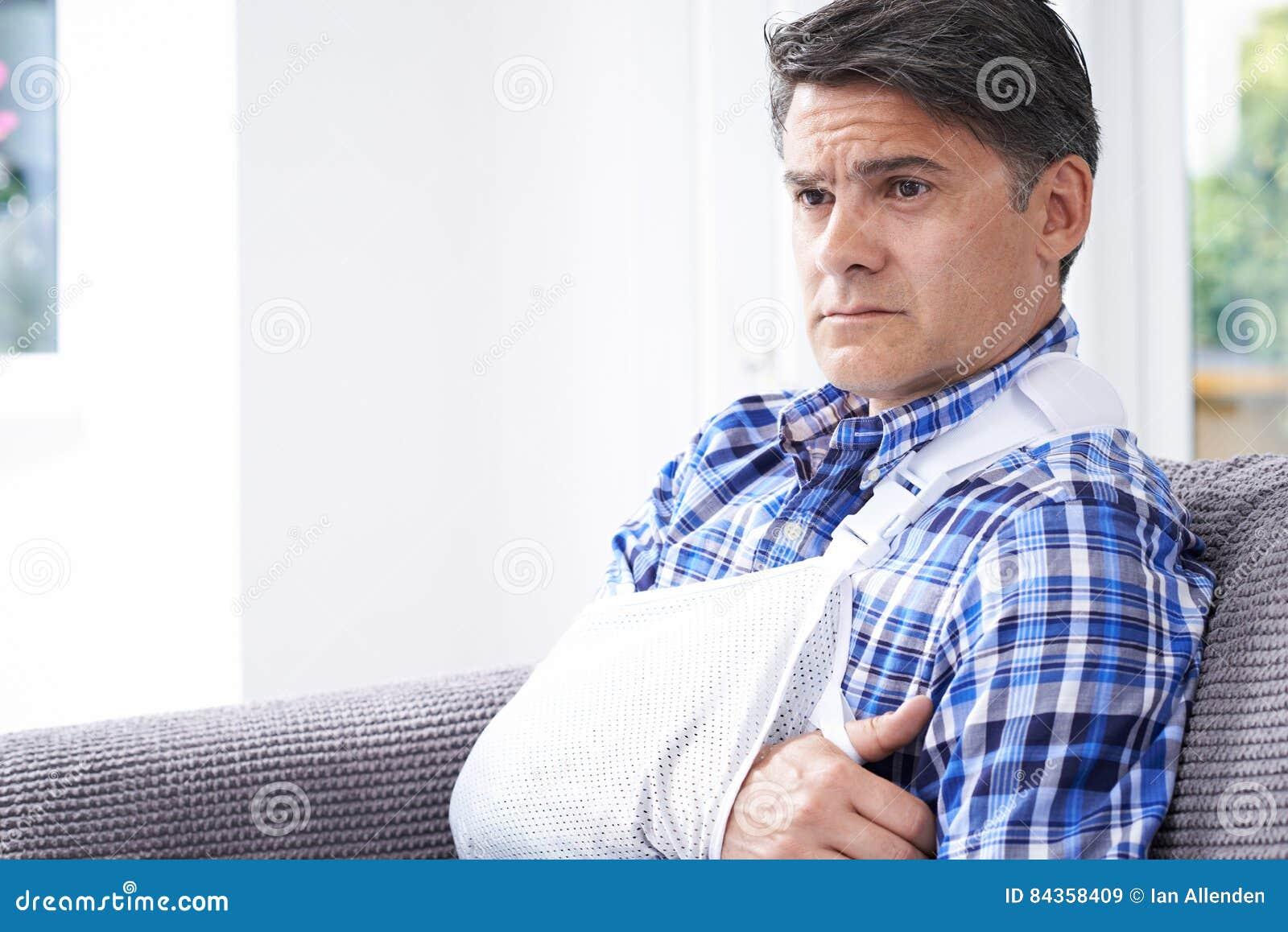 Зрелый человек с рукой в слинге дома