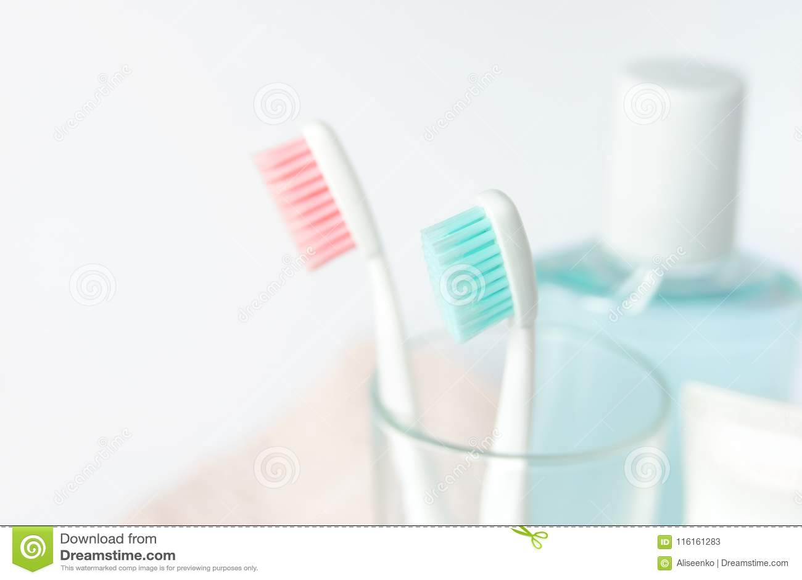Зубные щетки, зубная паста, rinse и полотенце на белой предпосылке