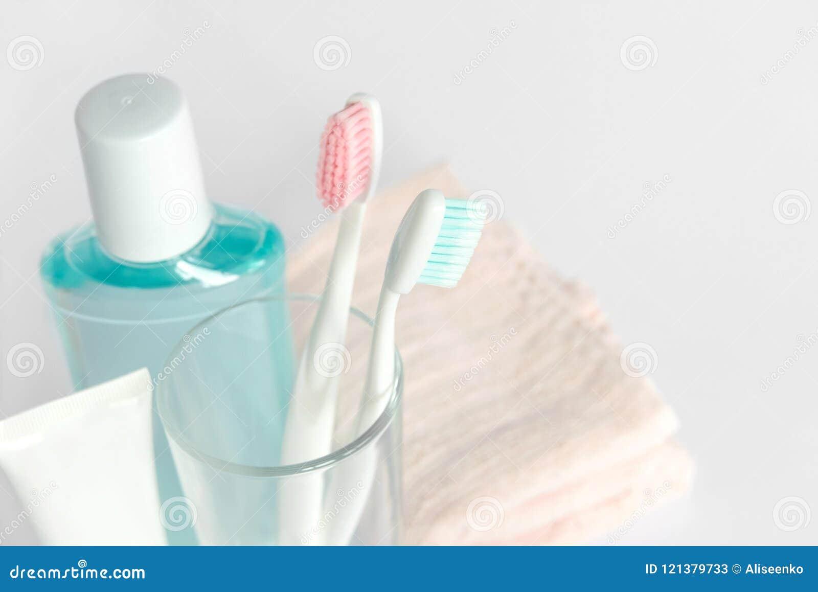 Зубные щетки, зубная паста, rinse и полотенце на белой предпосылке d