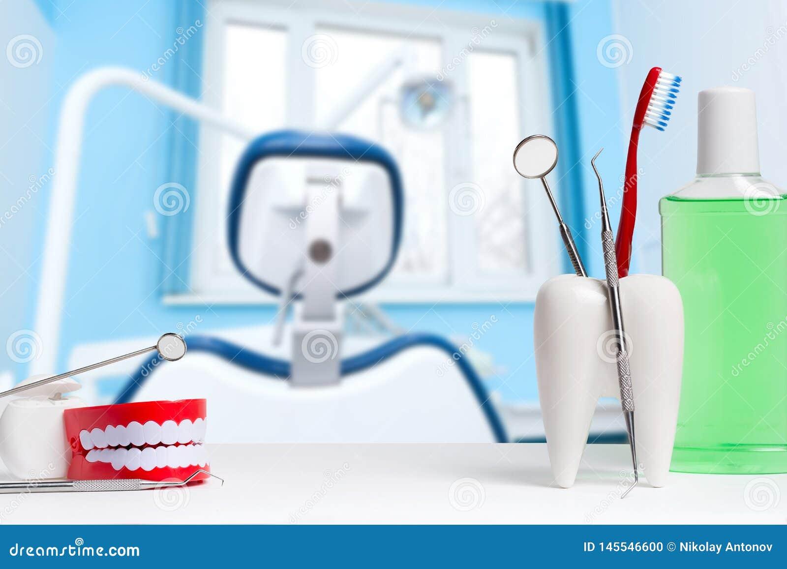 Зубоврачебная концепция здоровья и teethcare Зубоврачебное зеркало с зондом исследователя и зубная щетка в белой модели зуба окол