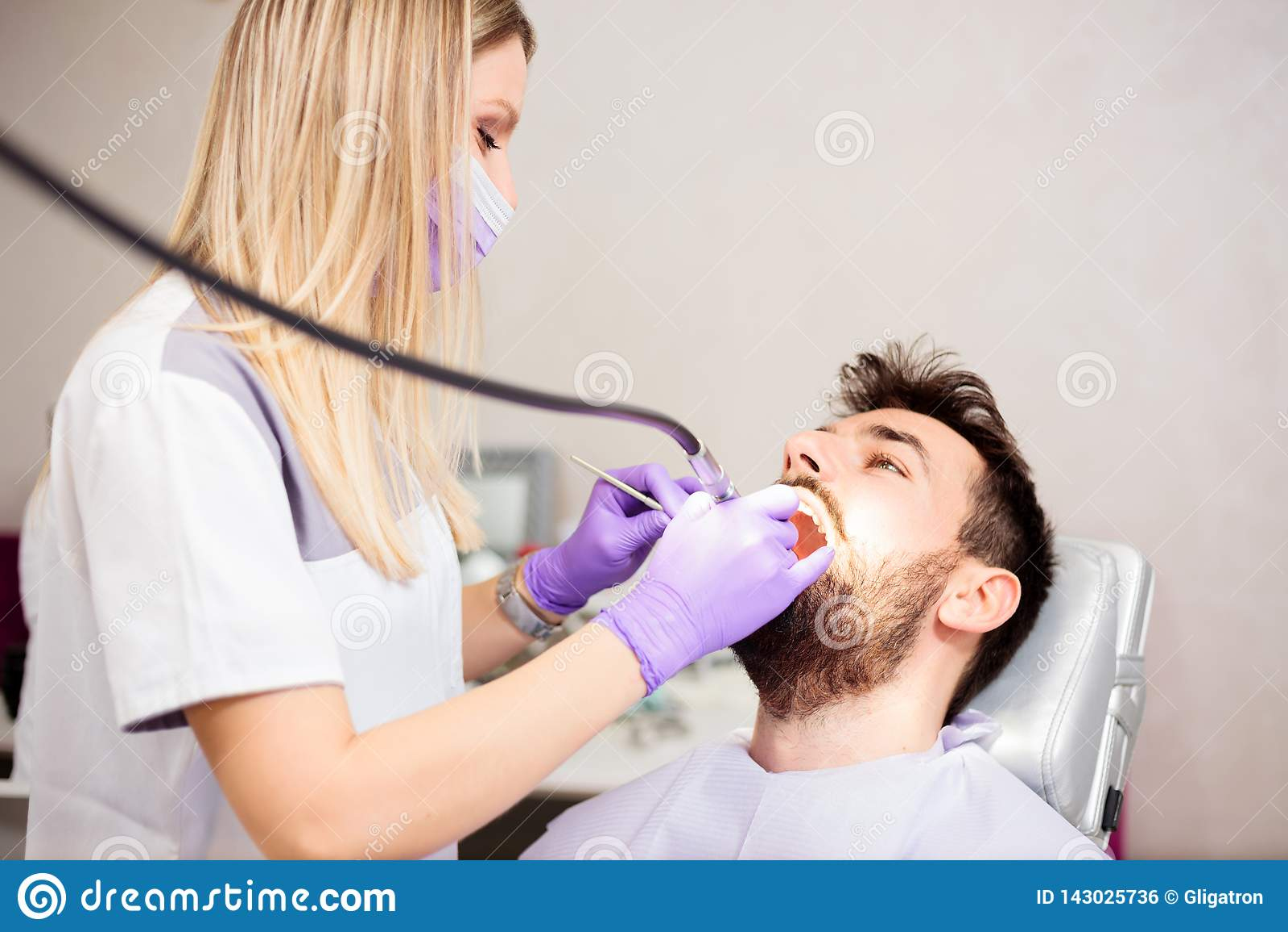 Зубы красивого молодого женского дантиста полируя молодого мужского пациента в зубоврачебной клинике