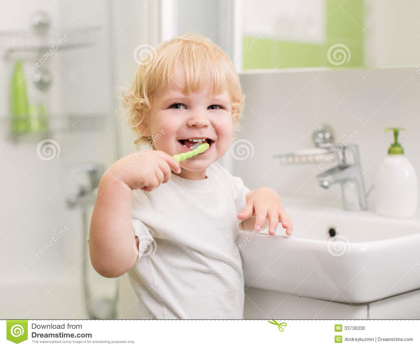 Зубы счастливого ребенк чистя щеткой в ванной комнате