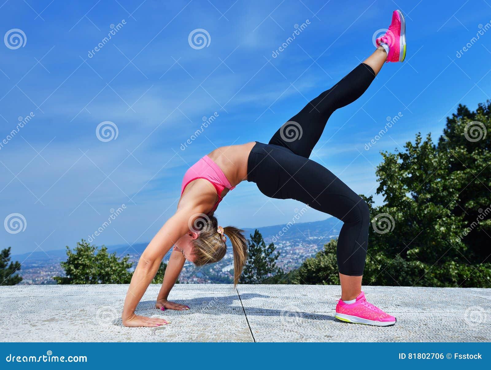 Здоровая молодая милая женщина протягивая ее ногу во время тренировки в парке