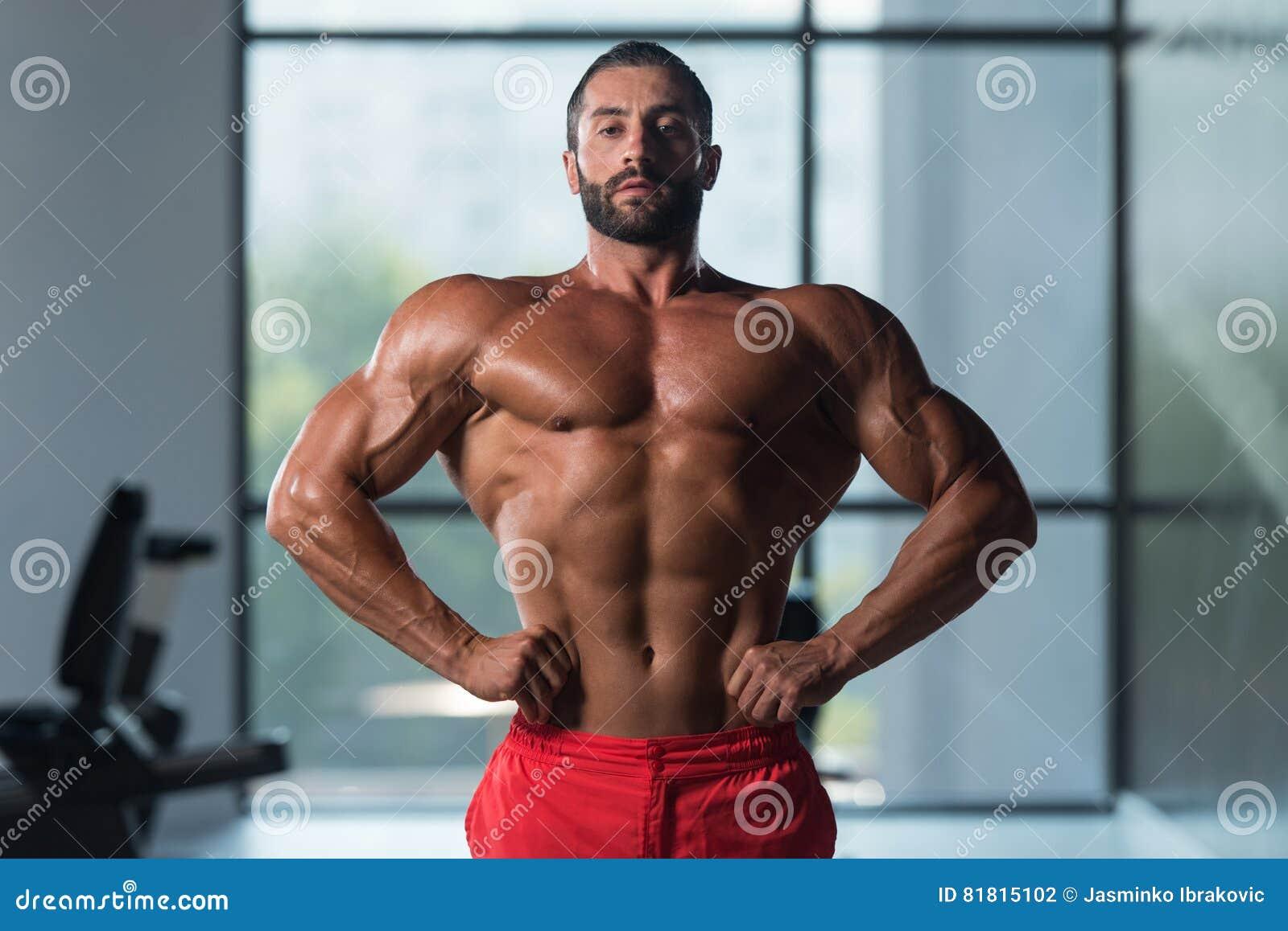 Здоровый молодой человек изгибая мышцы