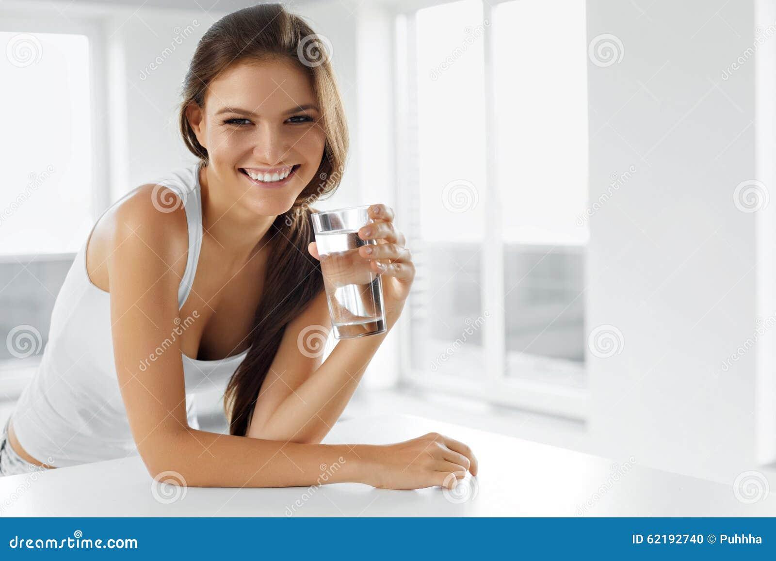 Здоровый уклад жизни Счастливая женщина с стеклом воды пить излечите