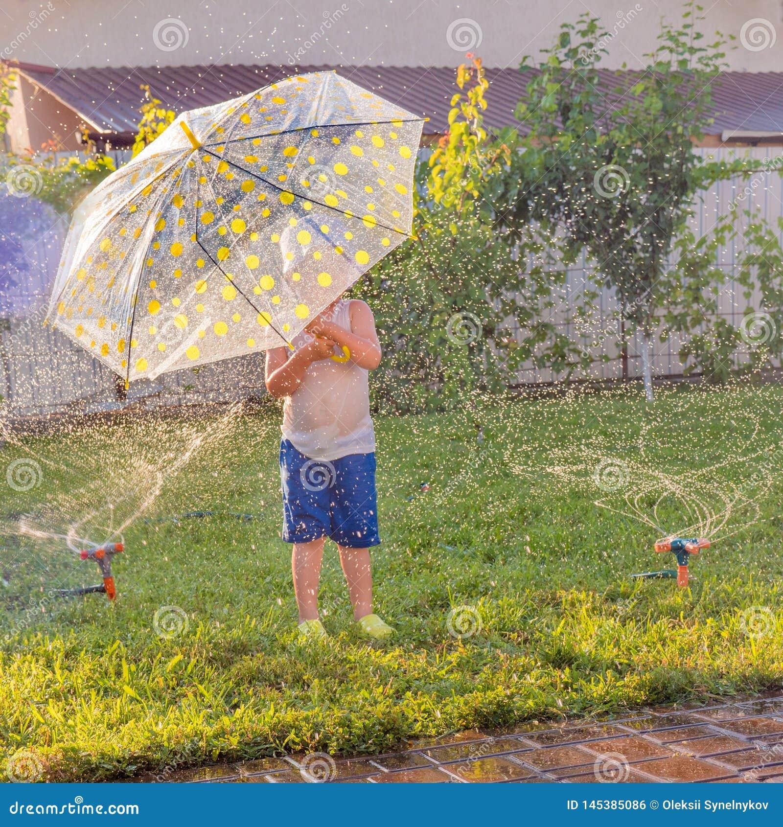 Мероприятия на свежем воздухе лета Игра детей на открытом воздухе на дворе перед входом Мальчик с зонтиком имея потеху около авто