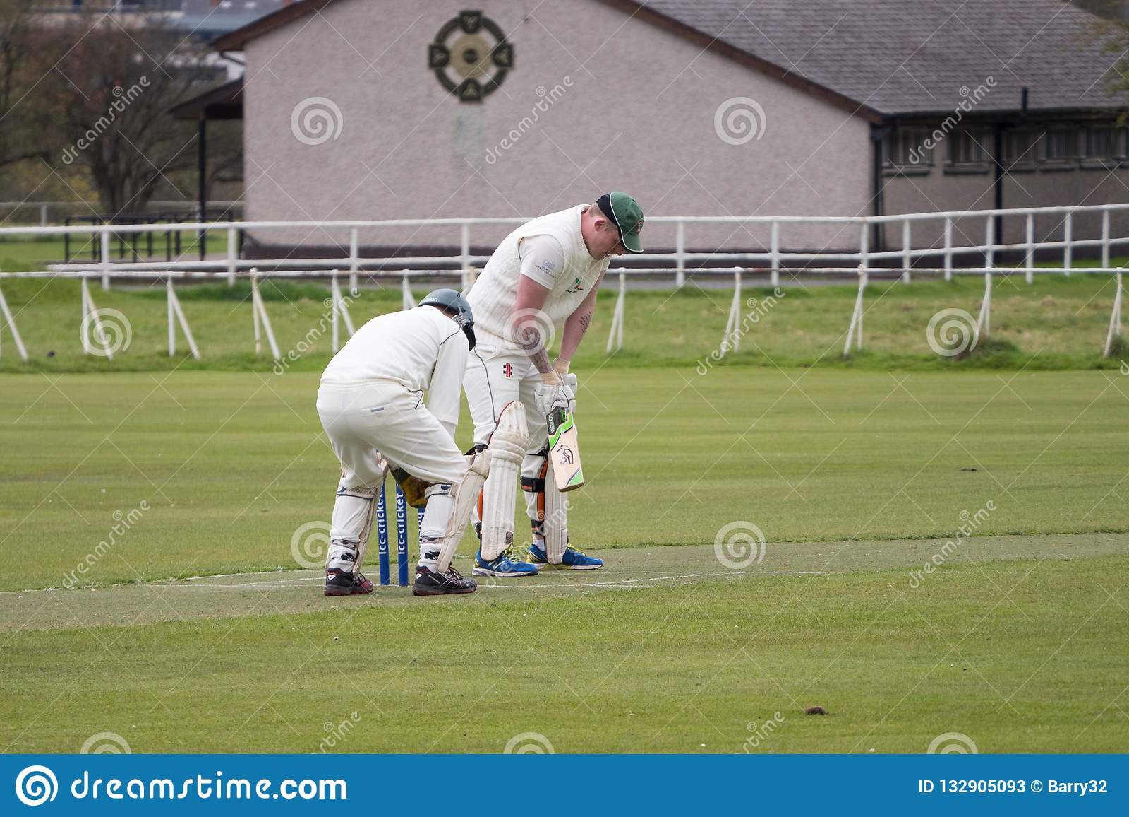 Игроки в крикет играя сверчка в парке