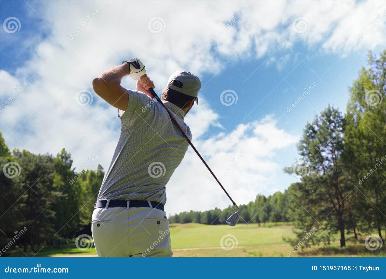 Игрок в гольф ударяя съемку гольфа с клубом на курсе пока на летних каникулах