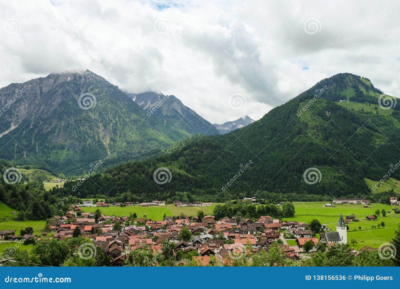 Идилличный ландшафт горы с небольшой деревней и горами на заднем плане