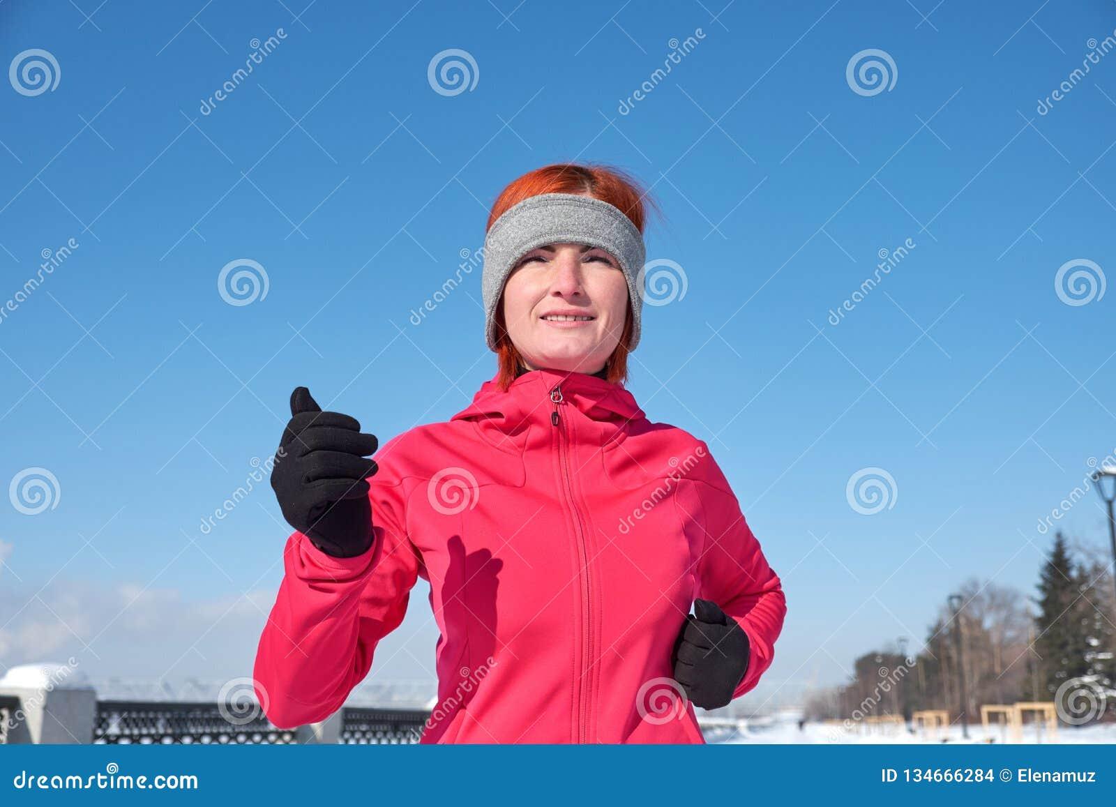 Идущая женщина спортсмена sprinting во время тренировки зимы снаружи в холодной погоде снежка Закройте вверх по показывать скорос