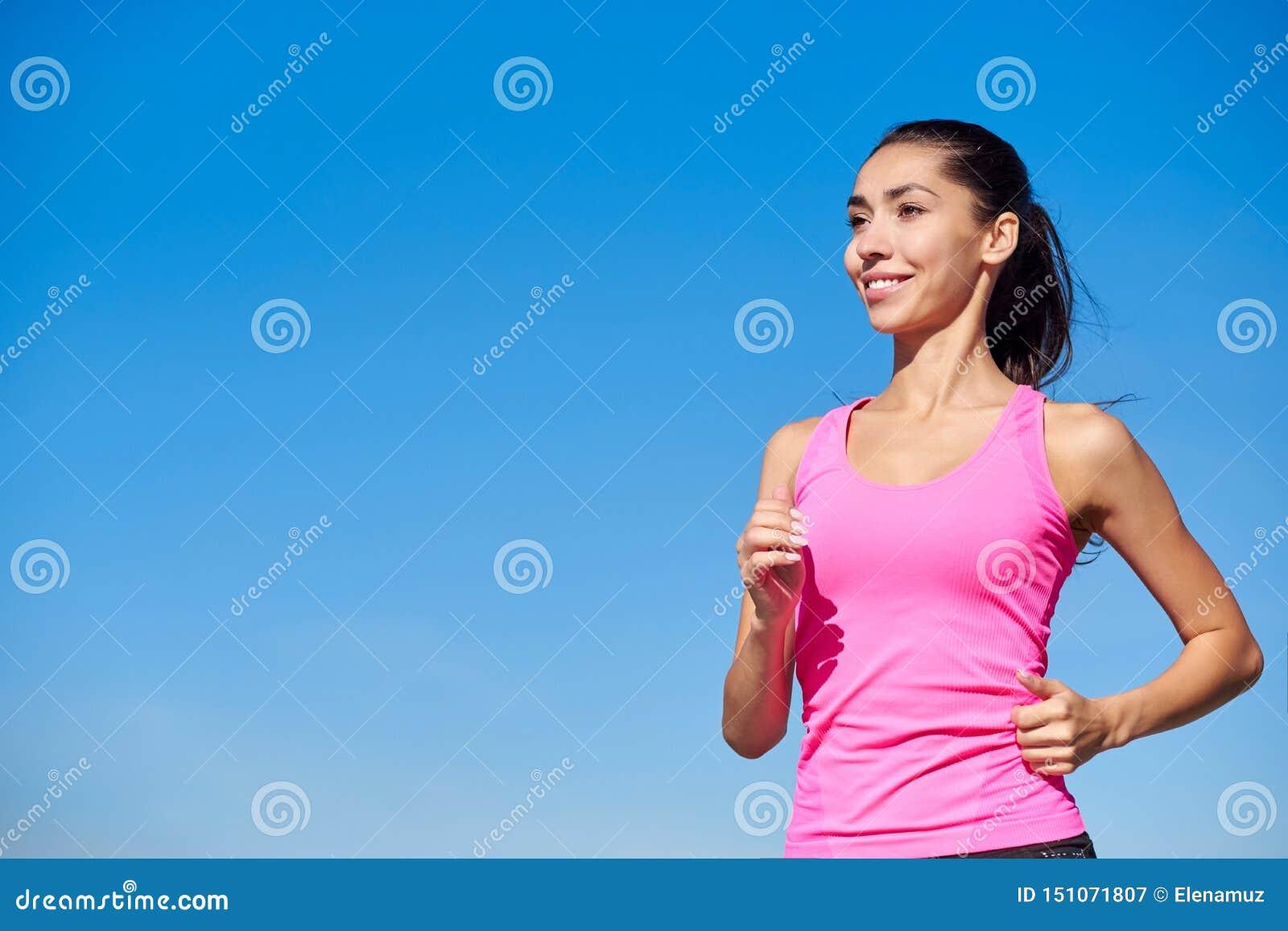 Идущая женщина фитнеса Тренируя женщина в розовой верхней части на голубой предпосылке