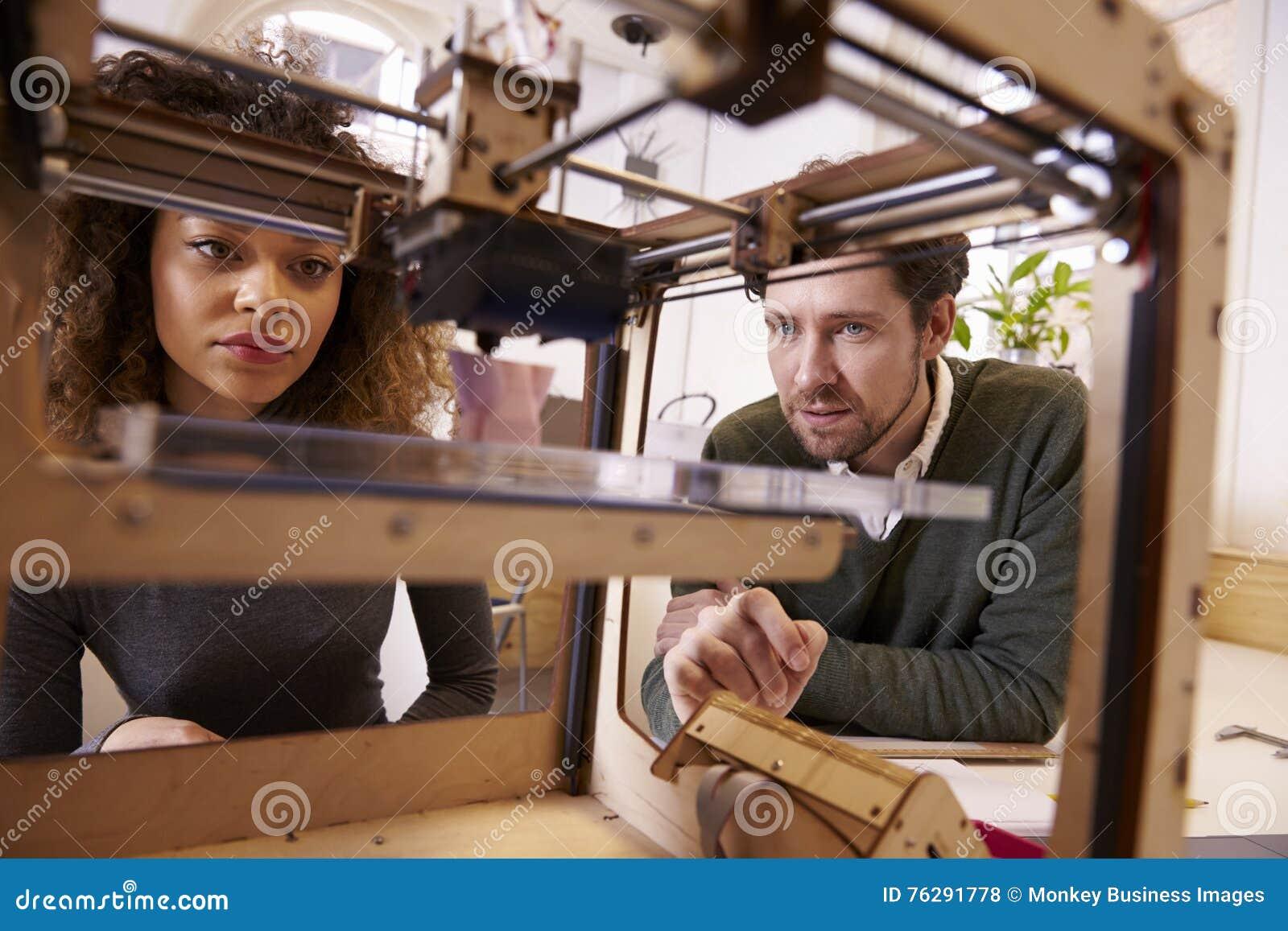 2 дизайнера работая с принтером 3D в студии дизайна