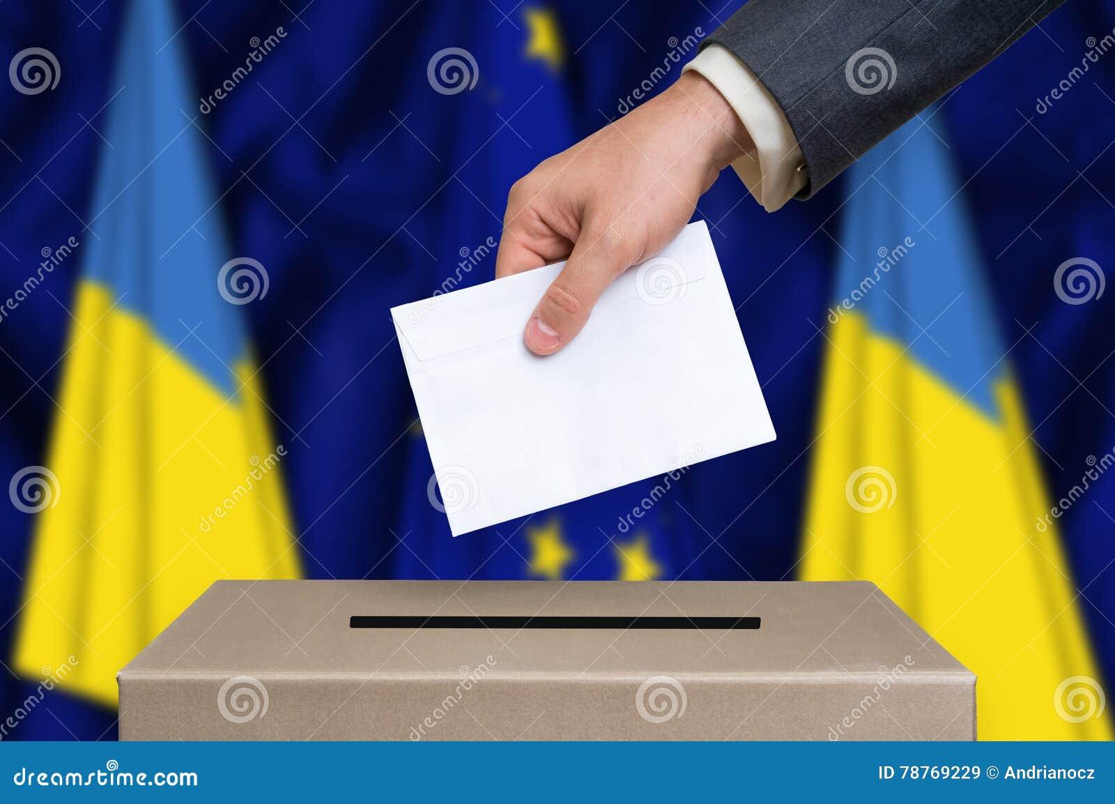 Избрание в Украине - голосующ на урне для избирательных бюллетеней
