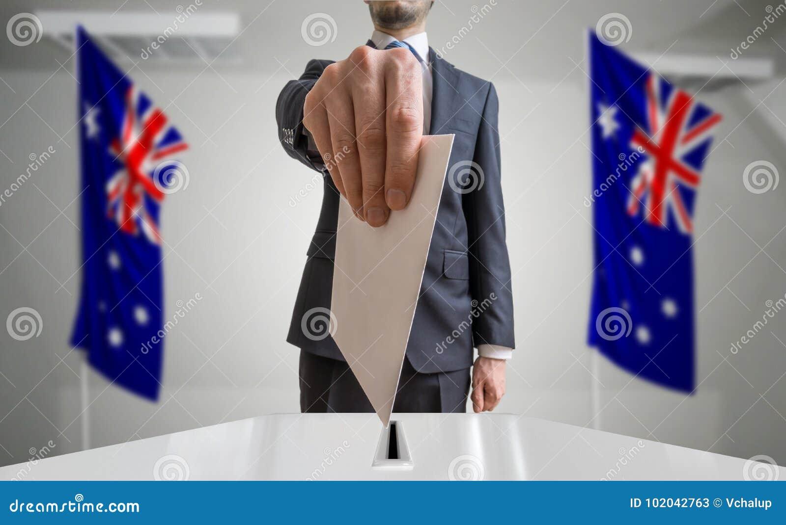 Избрание или референдум в Австралии Избиратель держит конверт в голосовании руки вышеуказанном Флаги австралийца в предпосылке