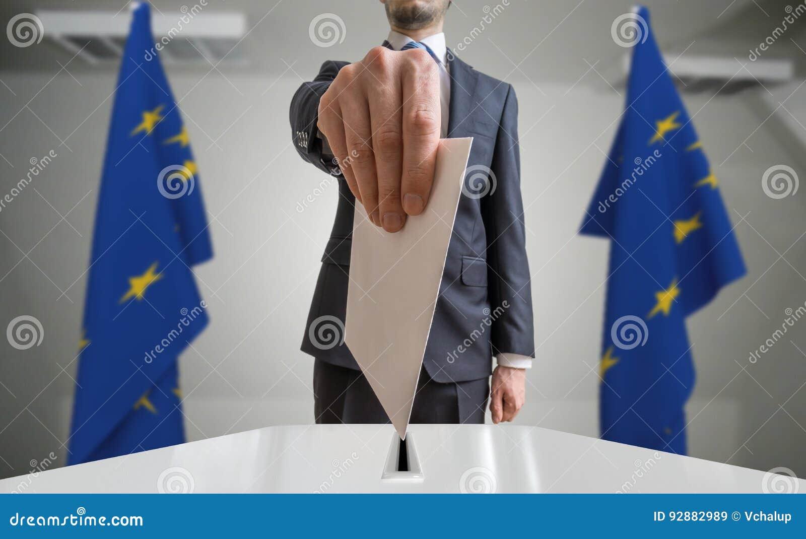 Избрание или референдум в Европейском союзе Избиратель держит конверт в голосовании руки вышеуказанном Флаги EC в предпосылке