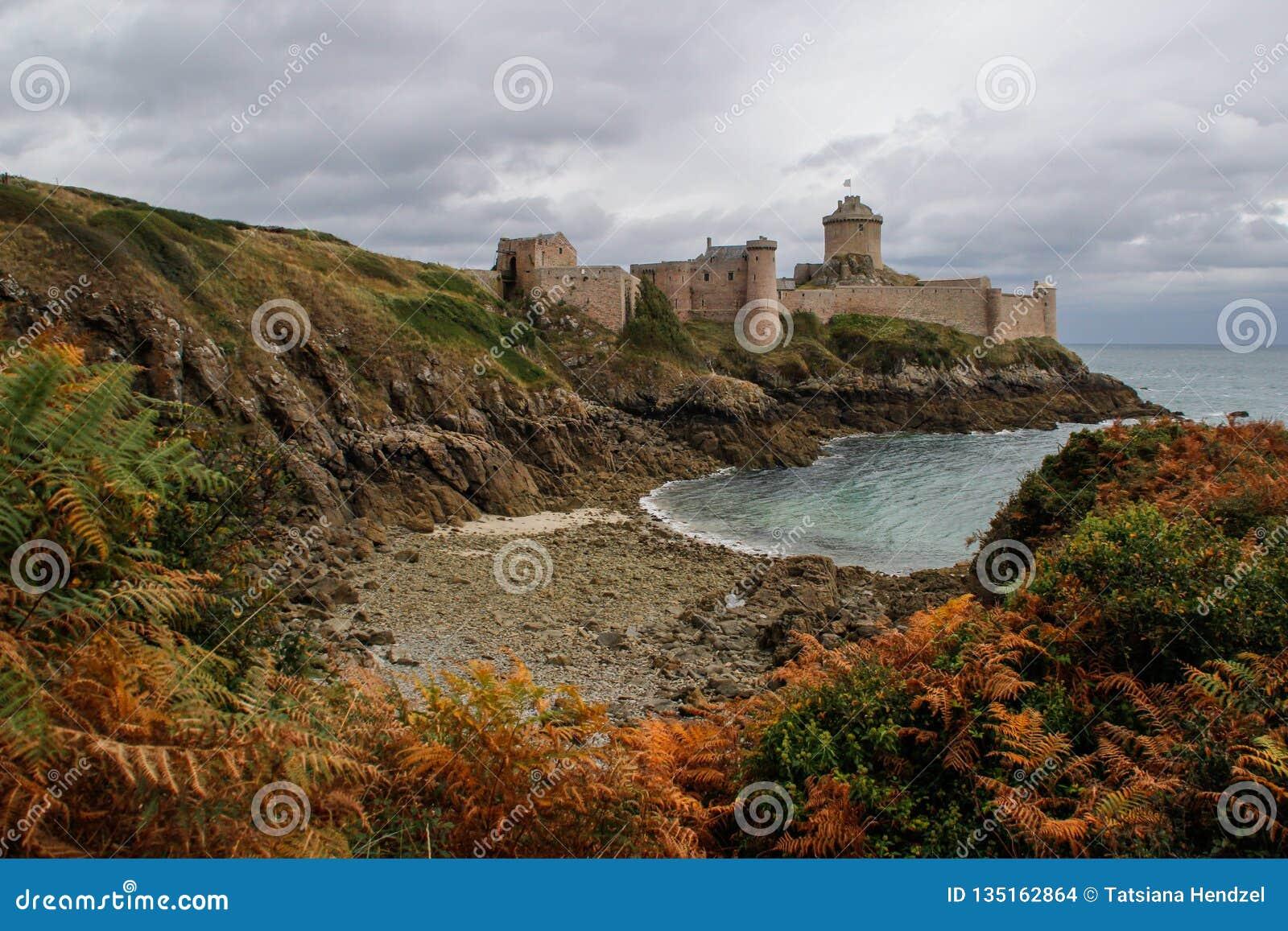 Известный средневековый каменный замок - Latte Ла крепости осенью во время шторма на кельтском море в Нормандии
