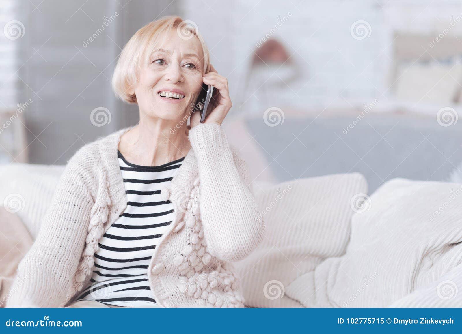 Излучающая старшая дама говоря на телефоне дома