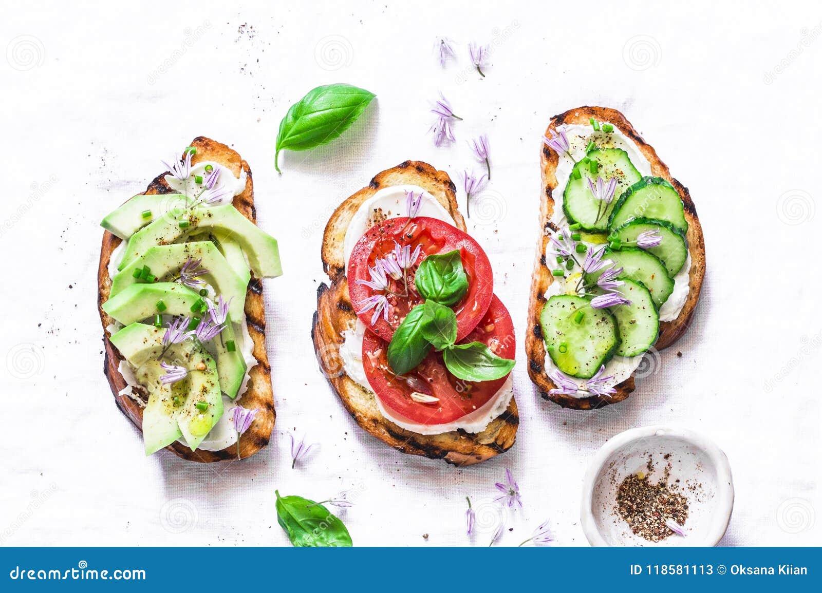 Изменения лета сандвичей - с плавленым сыром, авокадоом, томатом и огурцом на светлой предпосылке, взгляд сверху Здоровое питание