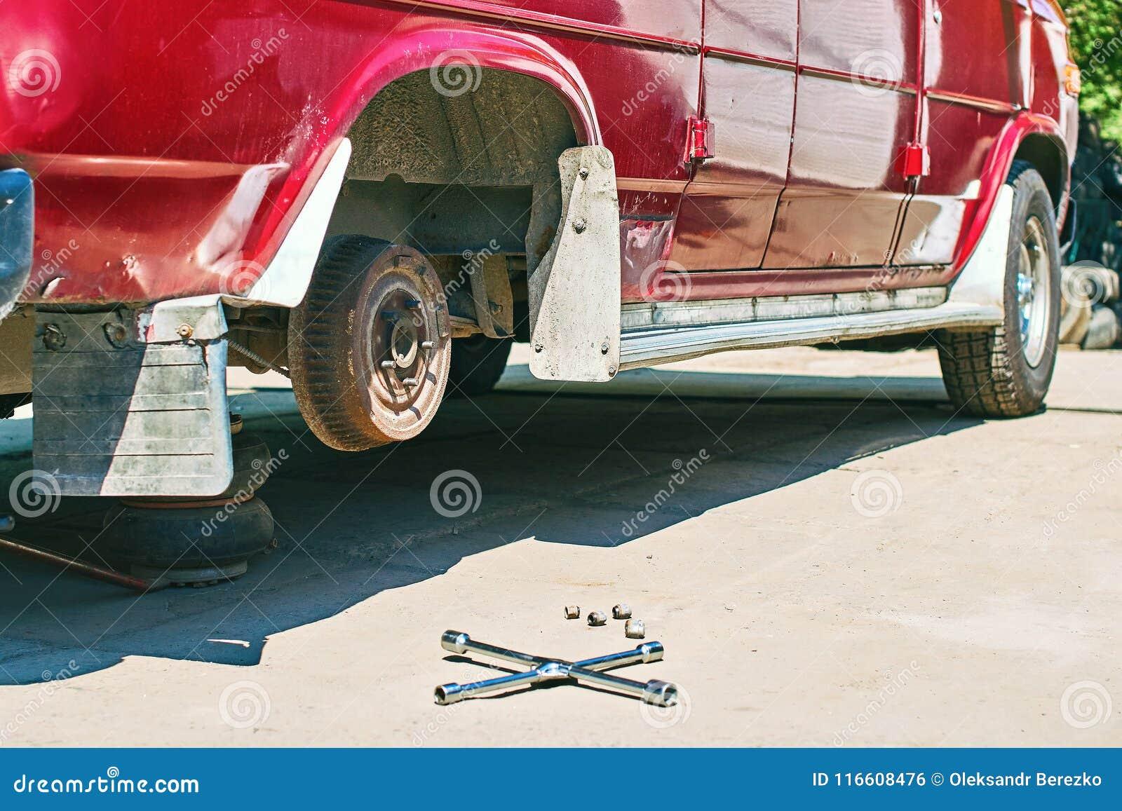 Изменять колесо или автошину на старом винтажном красном фургоне на внешнем обслуживании автомобиля