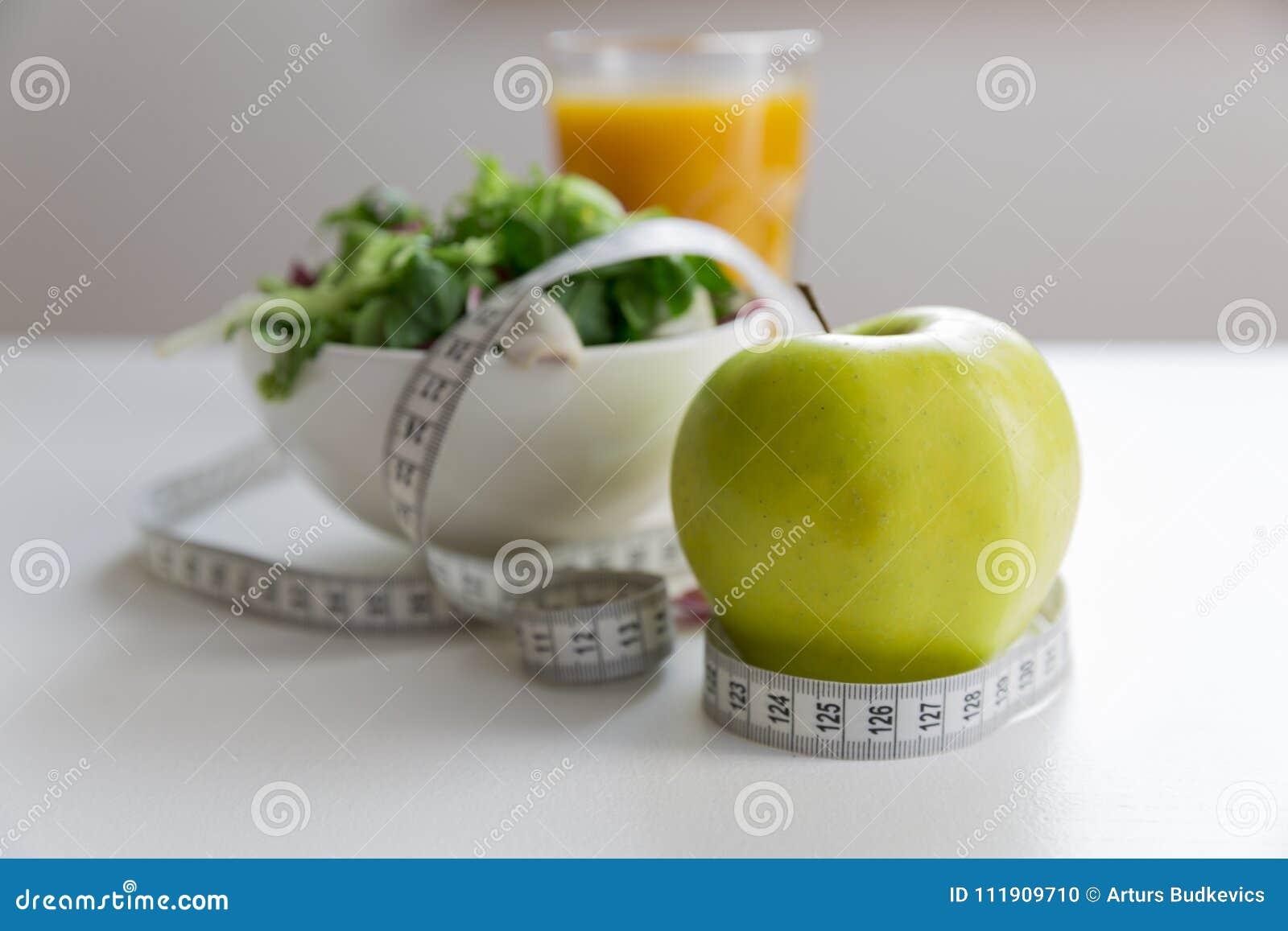 Измеряя лента вокруг яблока, шар зеленого салата и стекло сока Потеря веса и правая концепция питания