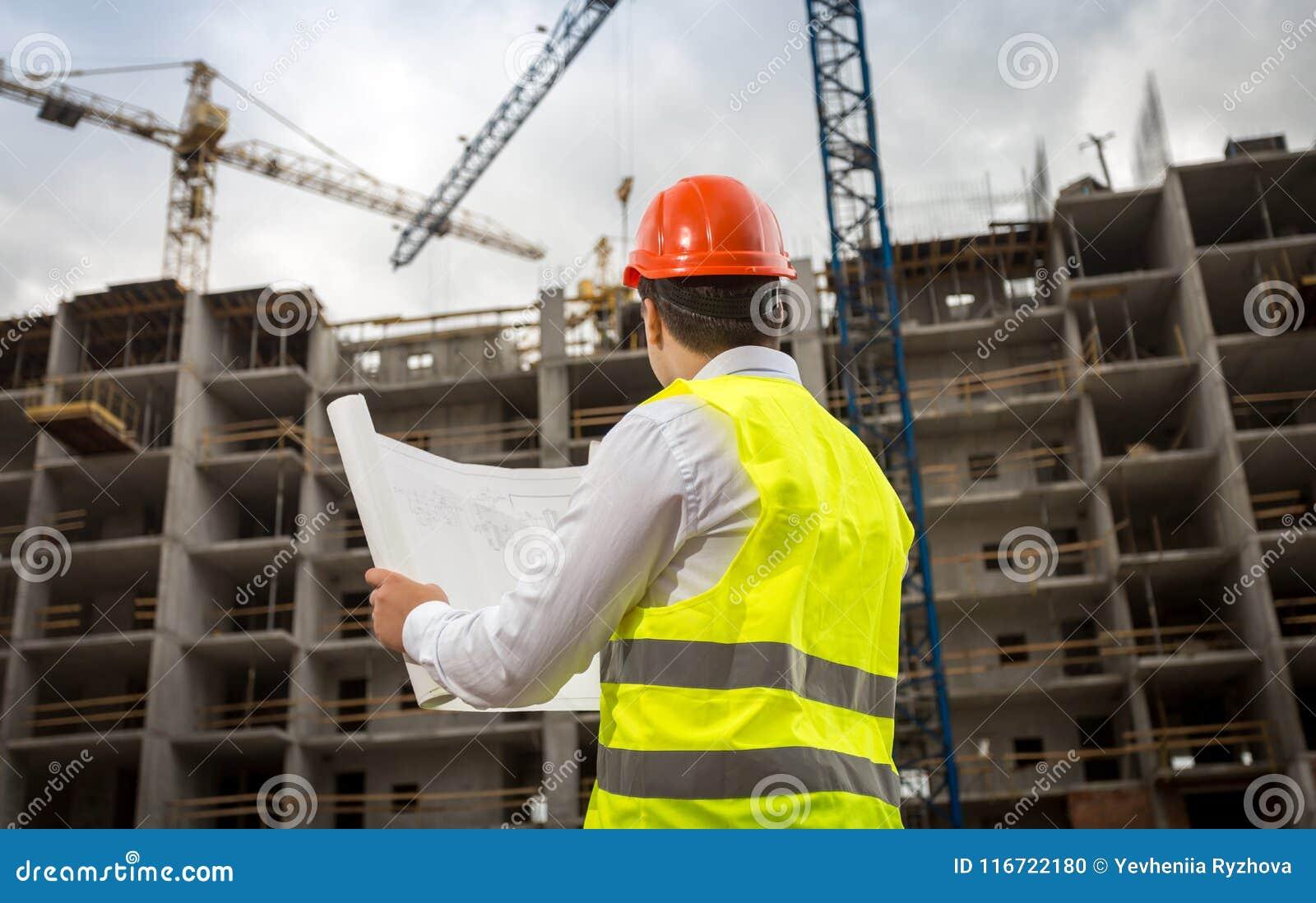 Изображение вид сзади инженера по строительству и монтажу смотря светокопии и работая вытягивает шею на строительной площадке