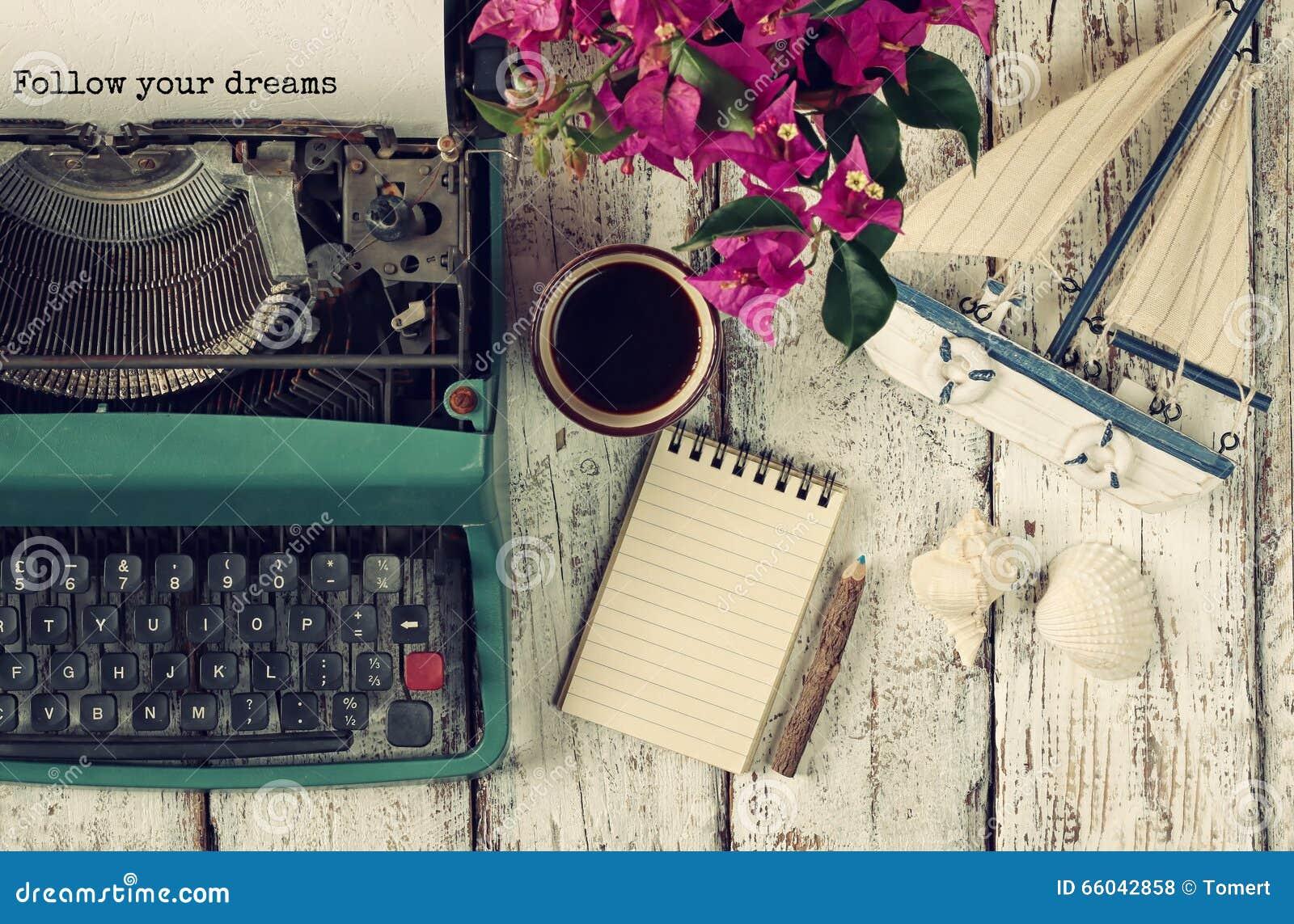 Изображение винтажной машинки с фразой следовать вашими мечтами, пустой тетрадью, чашкой кофе и старым парусником