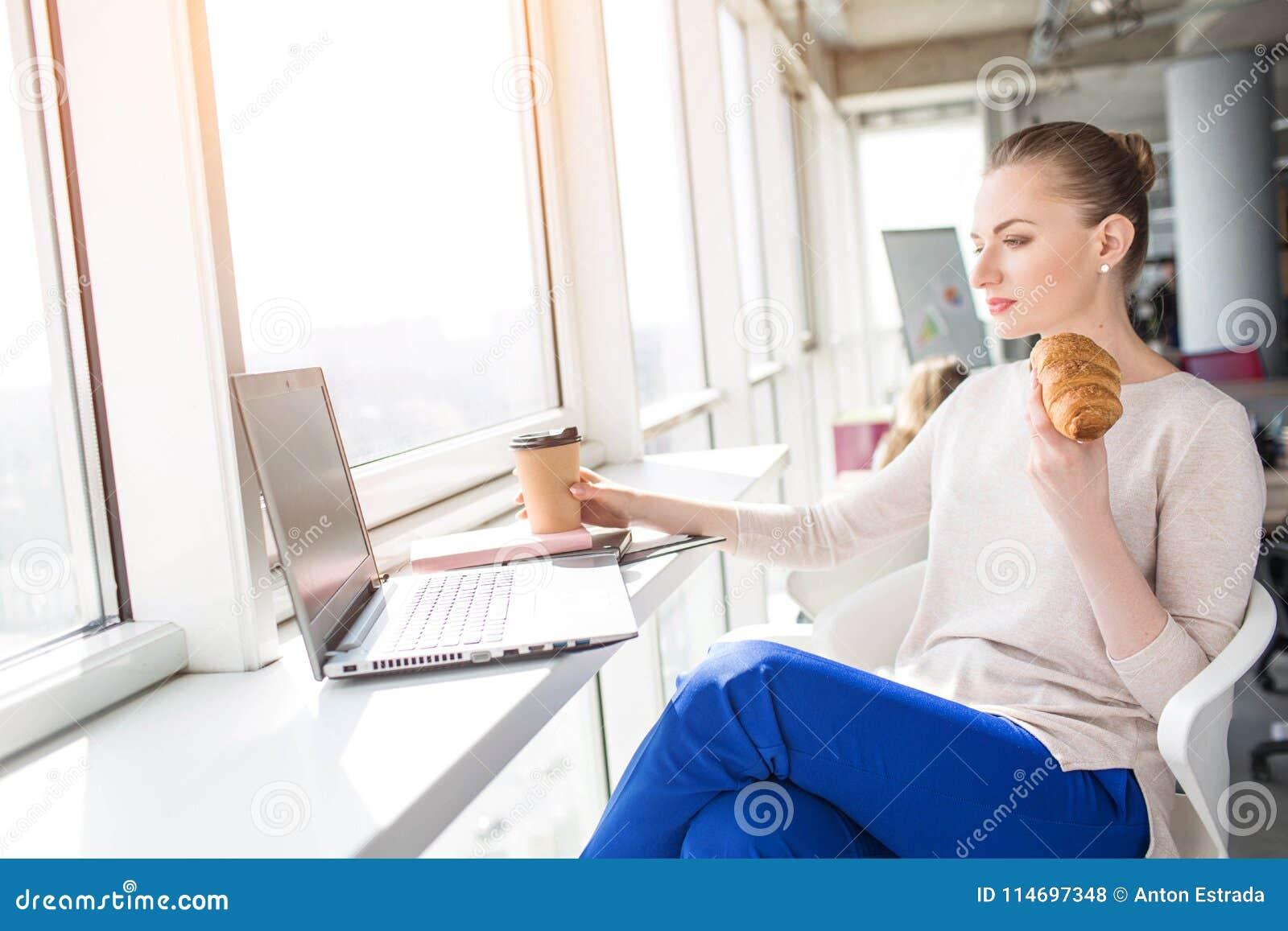 Девушка ест на работе заработать моделью онлайн в большой камень