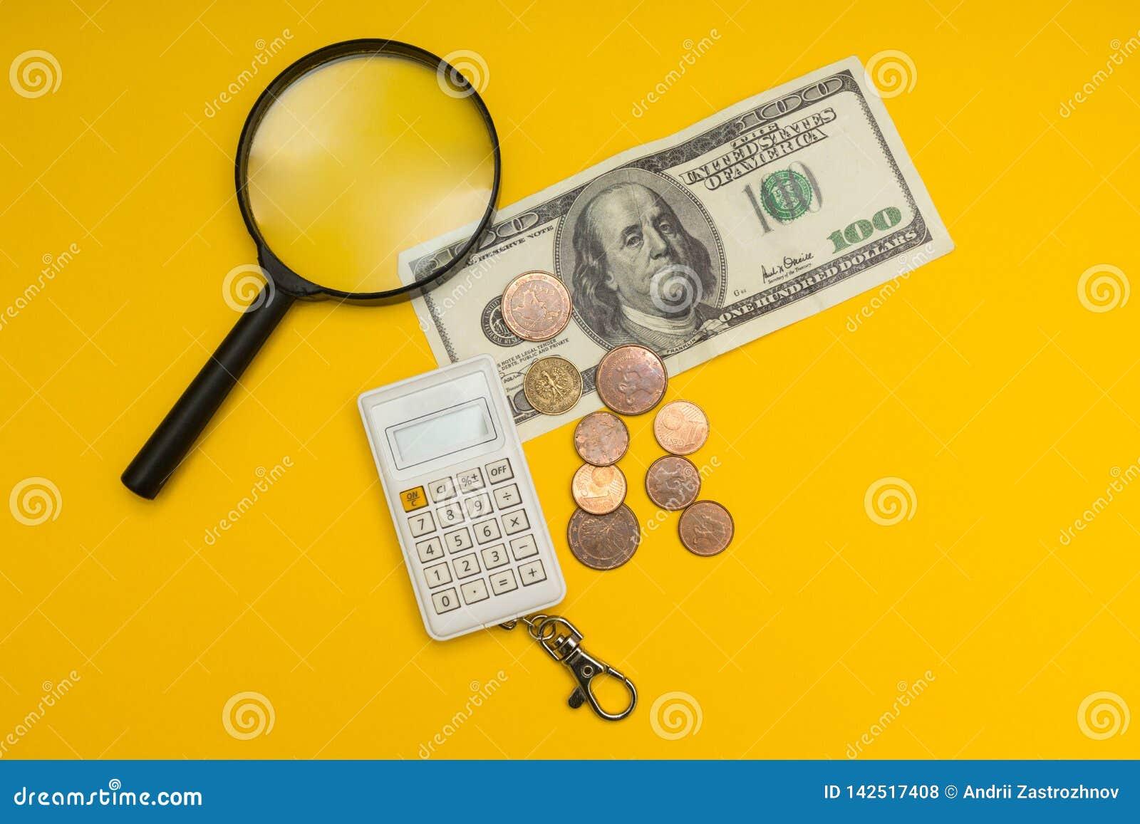Изображение концепции банкноты 100 долларов, лупы, калькулятора и монетки на желтой предпосылке