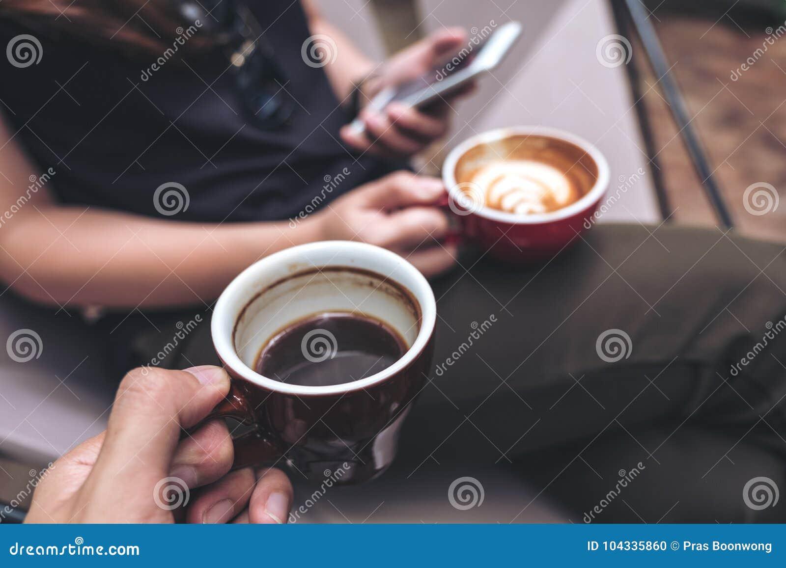 Изображение крупного плана руки ` s человека держа черную кофейную чашку при женщина используя smartphone пока выпивающ кофе