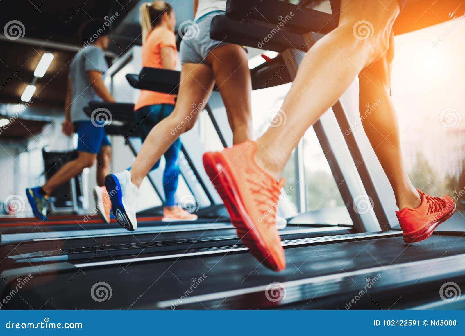 Изображение людей бежать на третбане в спортзале