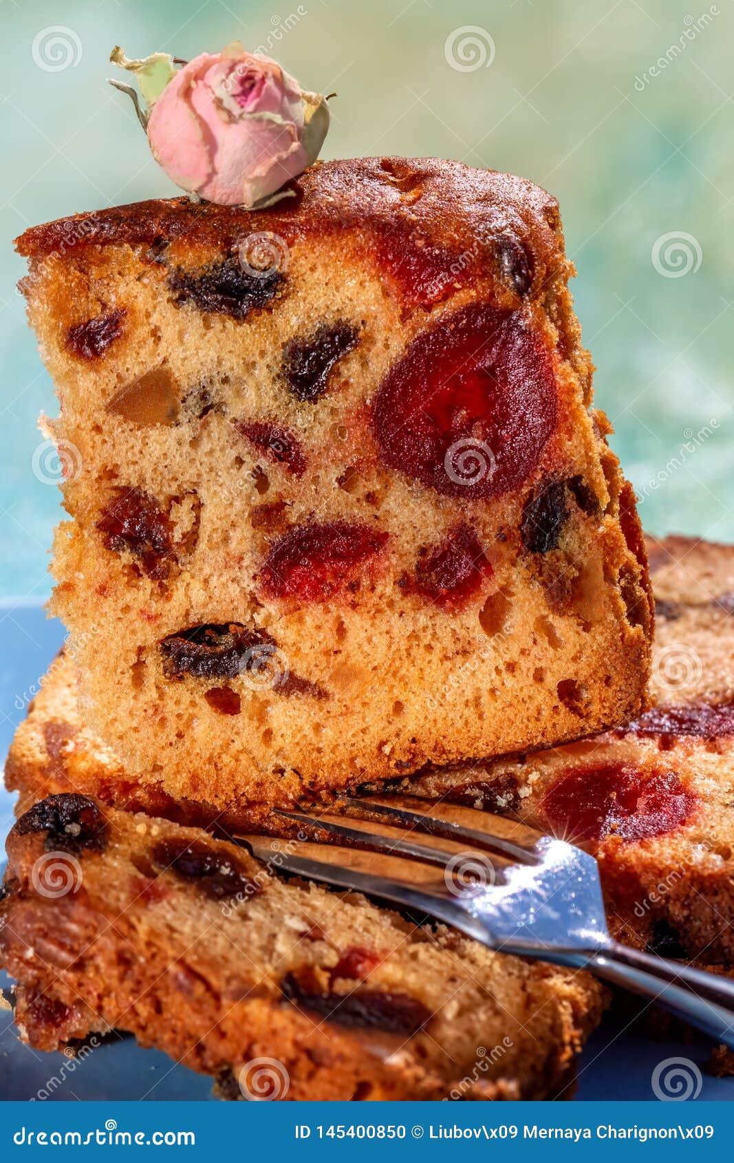 Изображение макроса куска торта с плодами и оформлением чая подняло Торт плода с изюминкой