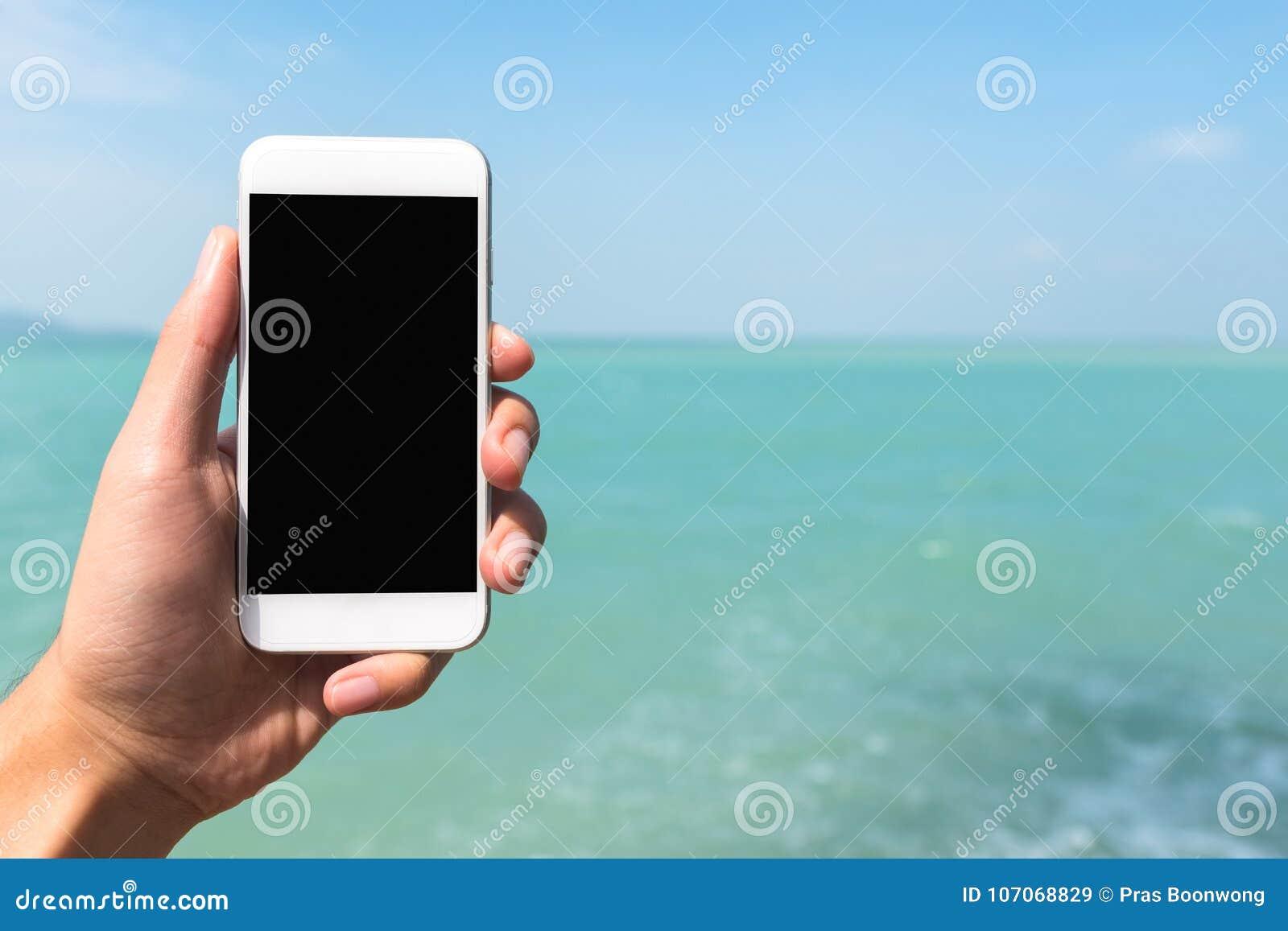 Изображение модель-макета руки держа и показывая белый мобильный телефон с пустым черным экраном настольного компьютера перед мор