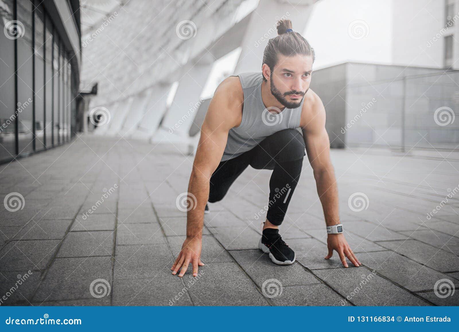Изображение молодого человека готовое для бега Он стоит в положении спринта и выглядит прямодушным Гай готов побежать быстро он