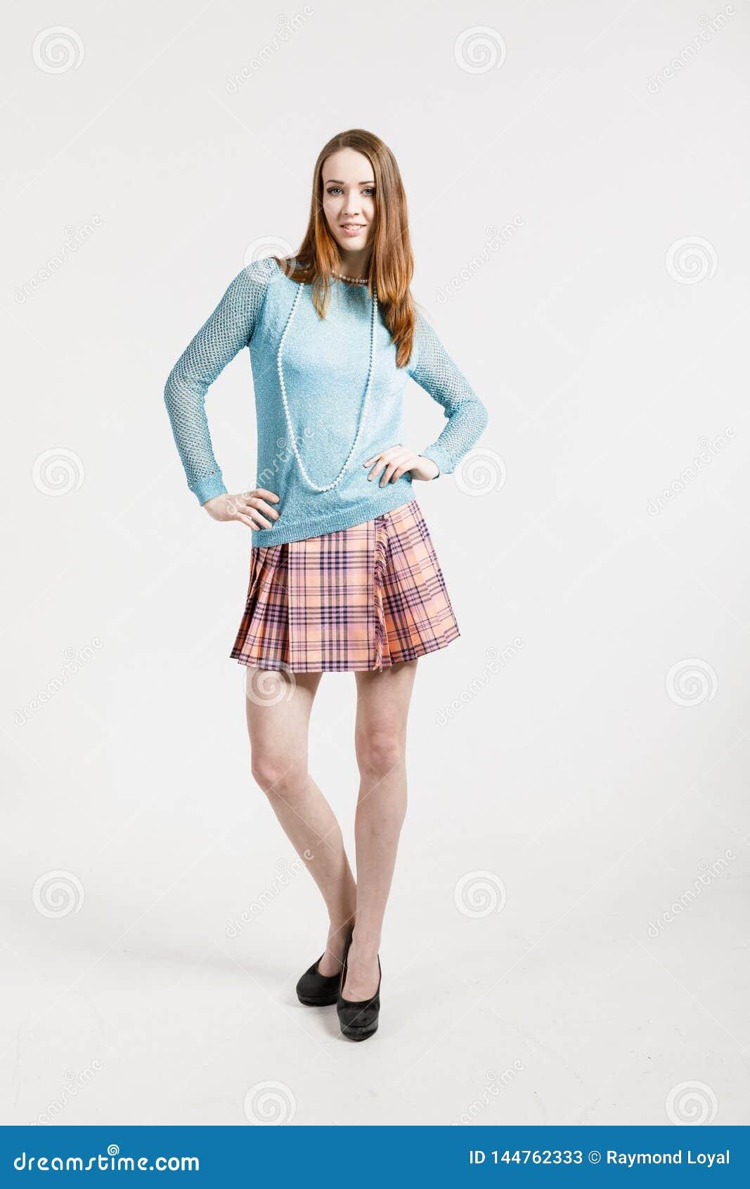 Изображение молодой женщины нося короткую юбку и пуловер бирюзы