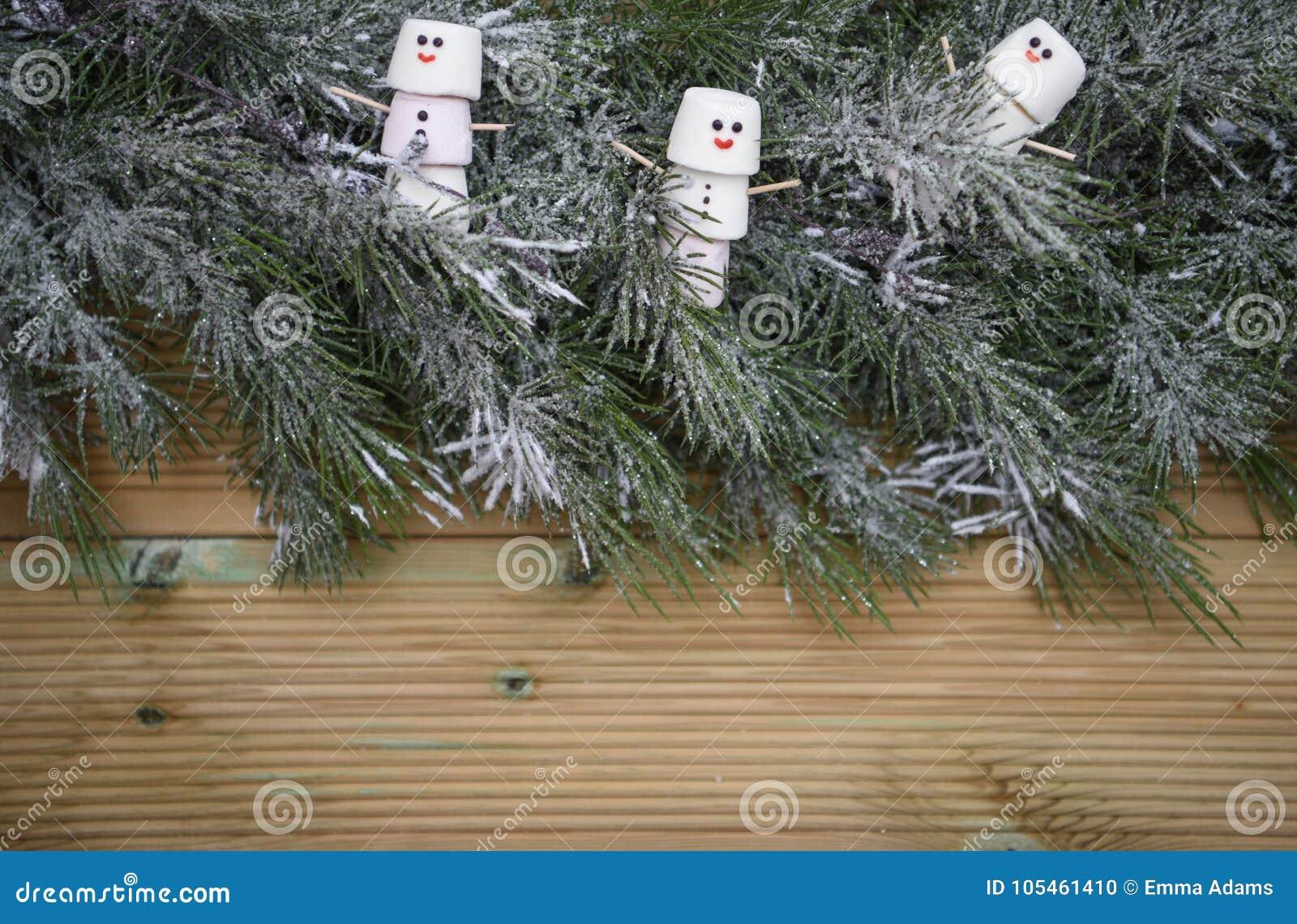 Изображение рождества потехи с зефирами как снеговик на украшении гирлянды взбрызнутом с снегом на деревянной предпосылке с космо