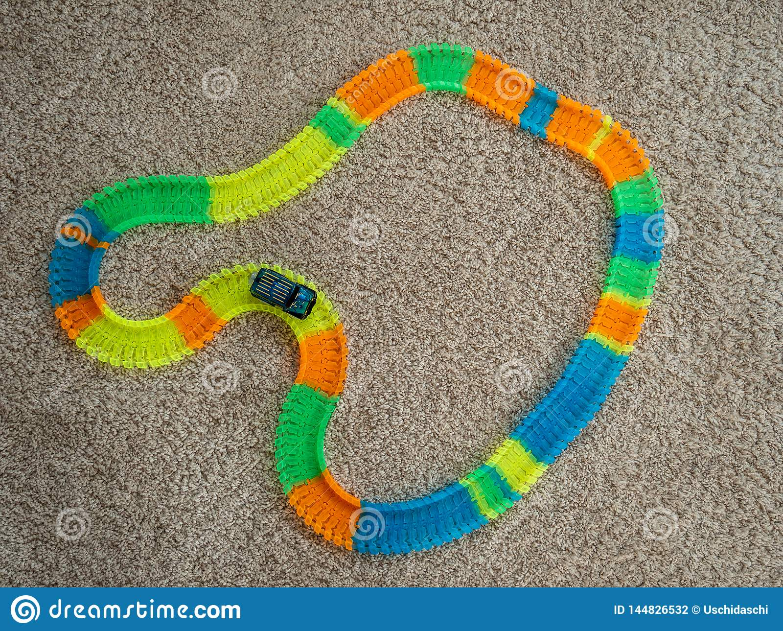 Изображение следа автомобиля игрушки с автомобилем и красочных элементов следа на ковре
