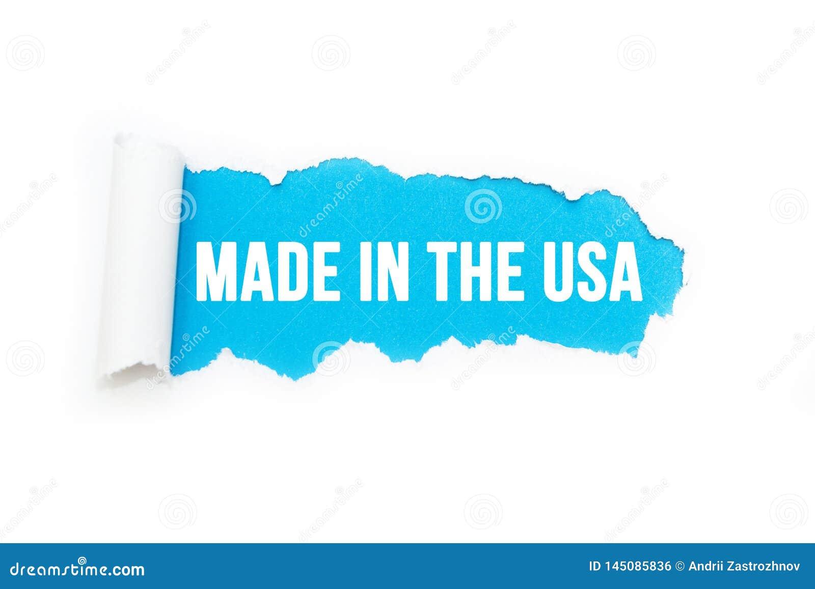 """Изолированная надпись """"сделанная в США """"на голубой предпосылке, рвя"""