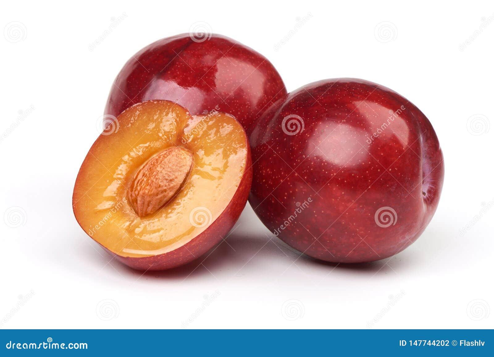 Изолированные сливы Полтора красного плода сливы с листьями изолированными на белой предпосылке