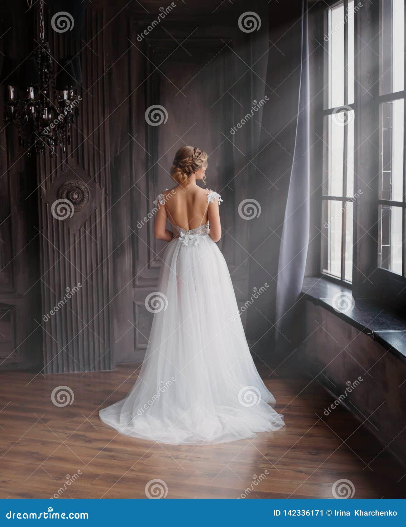 Изумительная дама в длинном белом прелестном дорогом светлом платье с поездом и открытых задних стойках с задней частью к камере,
