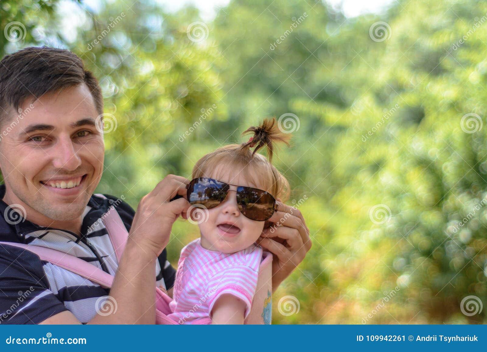 Изумительная маленькая девочка играет с солнечными очками с ее отцом