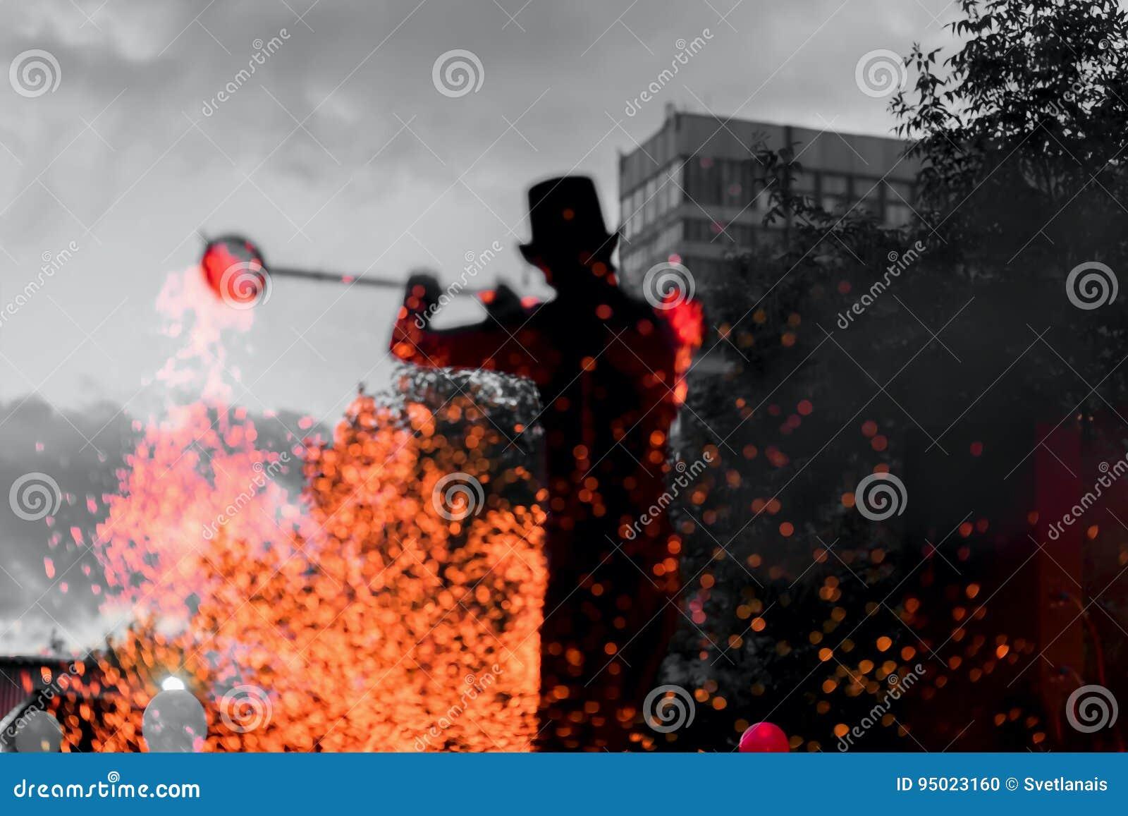 Изумительная выставка пожара на ноче Силуэт мастерского факира с работами огня Танец представления огня, волшебной концепции