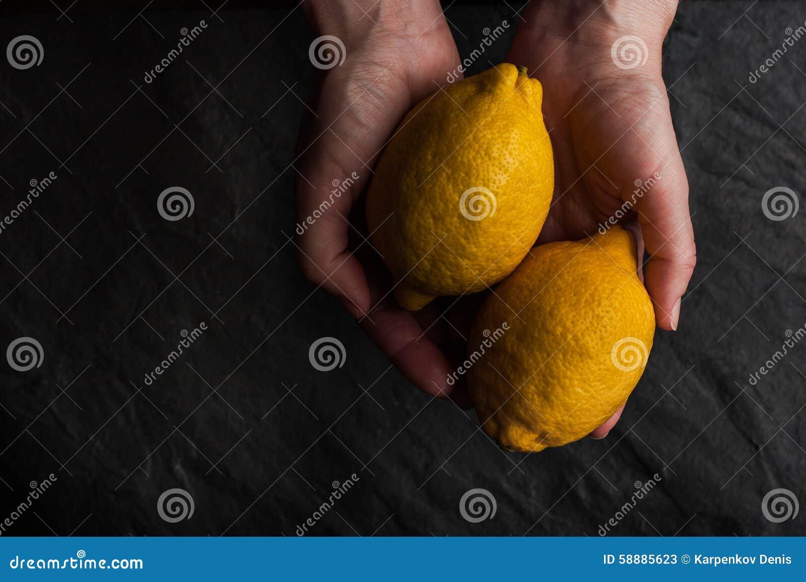 2 лимона в руках на черной каменной таблице