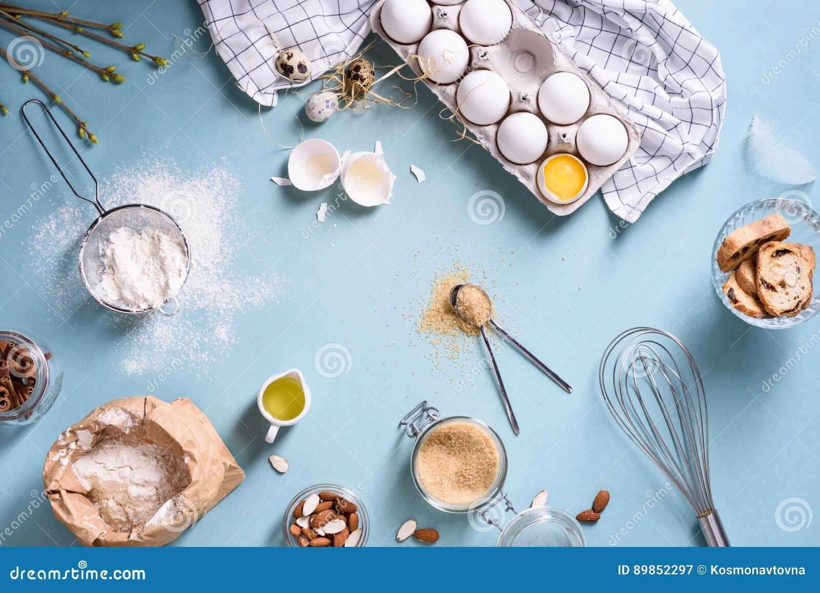 Ингридиенты хлебопекарни - мука, яичка, масло, сахар, желток, гайки миндалины на голубой таблице Сладостная концепция выпечки печ