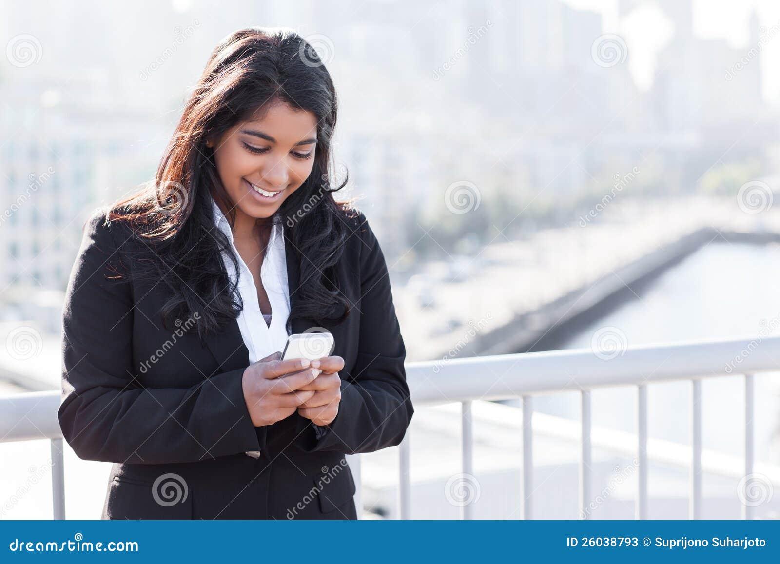 Индийская коммерсантка texting на телефоне