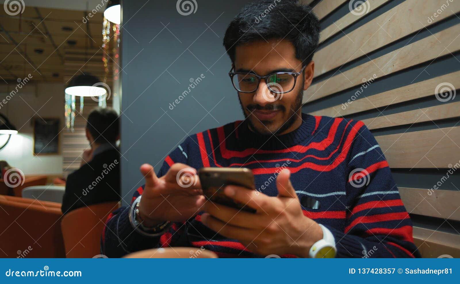 Индийский парень просматривает новости на смартфоне и улыбках пока сидящ на кафе сток-видео
