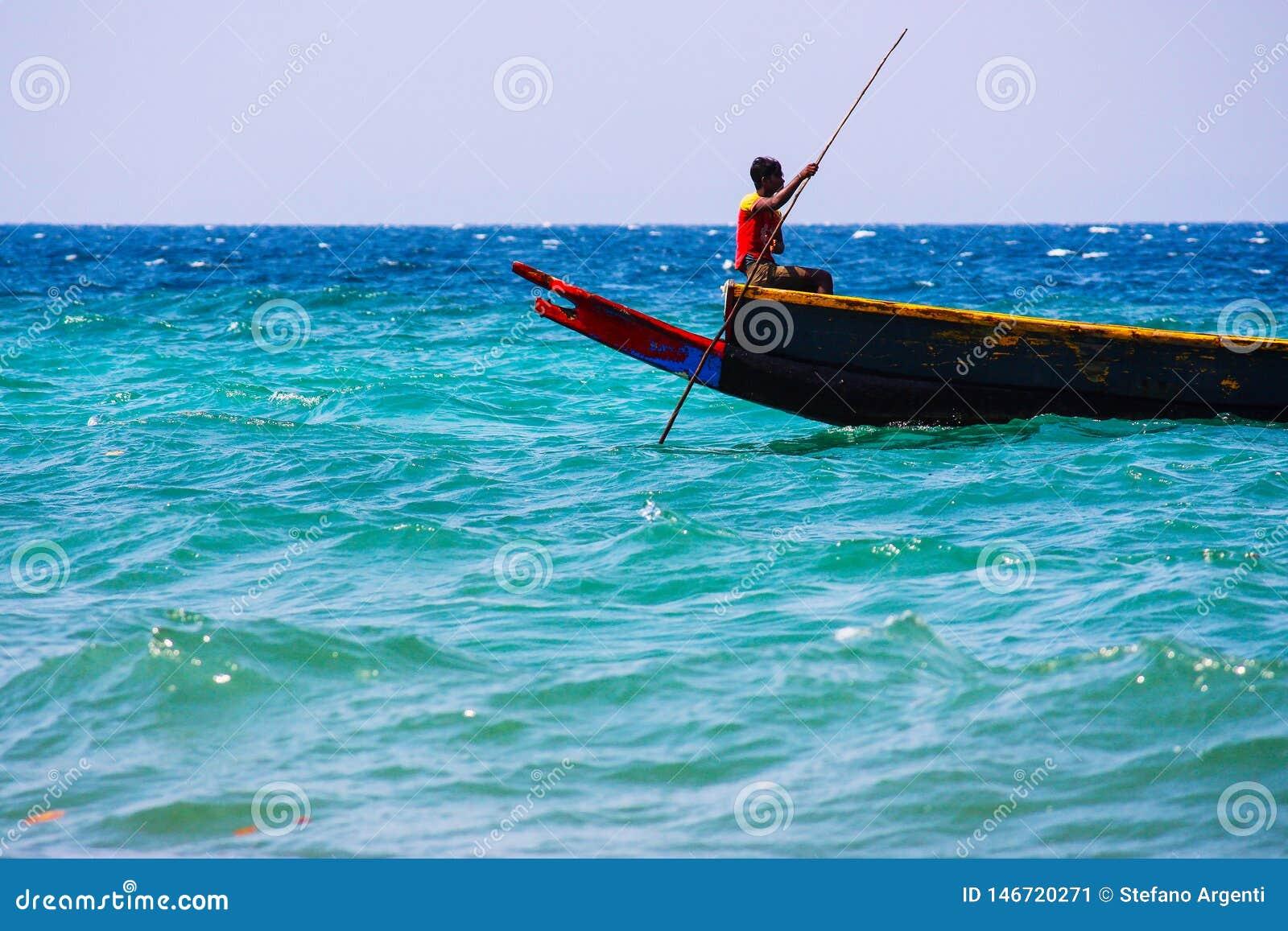 Индийский рыболов на его шлюпке в море