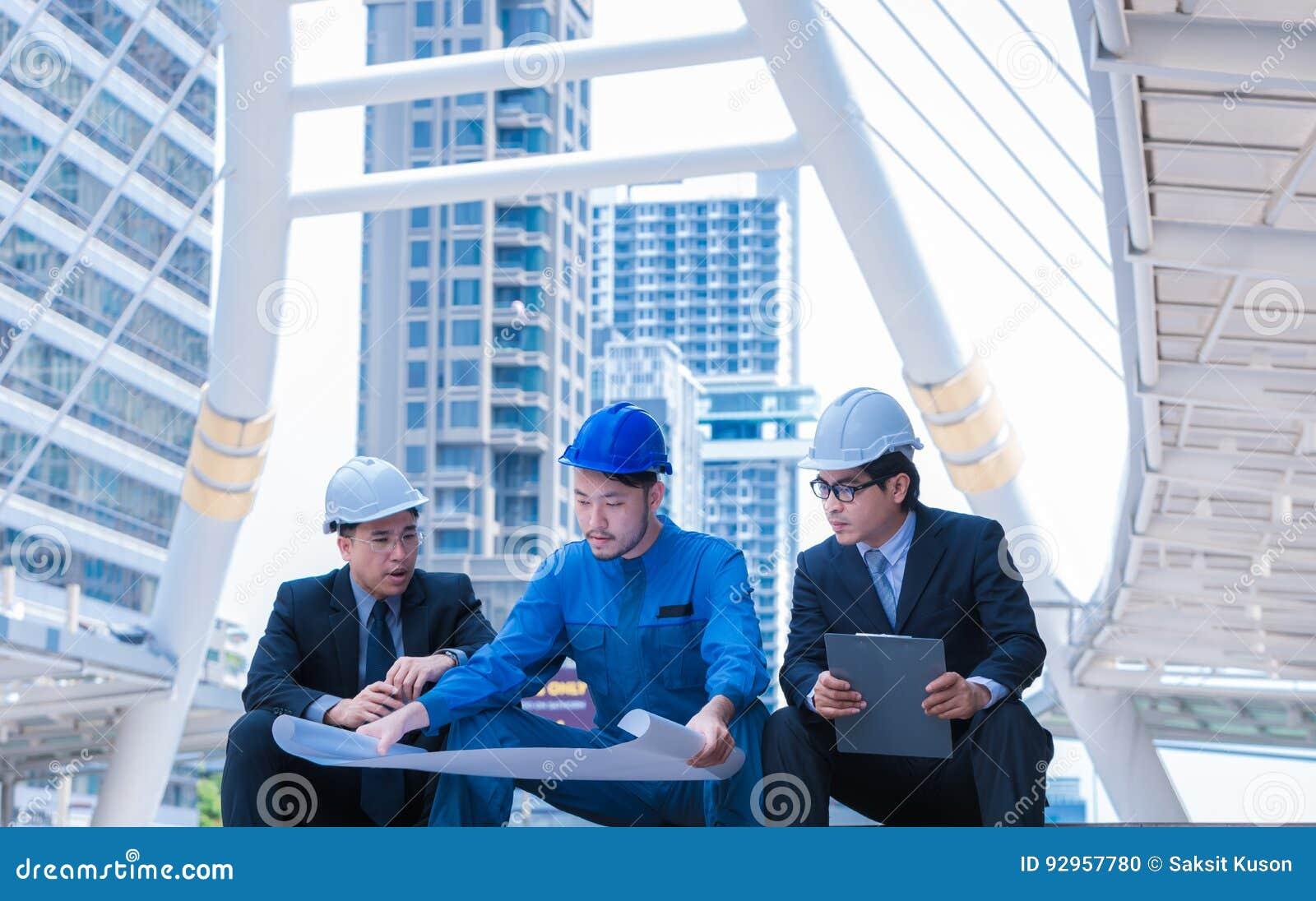 Инженеры встречая на террасе na górze строительной площадки Сотрудники обсуждая Босс и работник спорят Переговор в команде